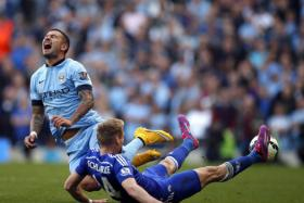 Chelsea's Andre Schurrle (R) challenges Manchester City's Aleksandar Kolarov during their English Premier League soccer match at the Etihad stadium in Manchester, northern England Sept 21.