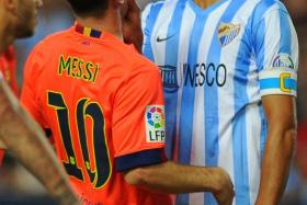 Malaga defender Weligton (right) grabs Lionel Messi during an argument.
