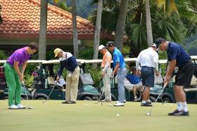 WARMING UP: Local amateur golfers on the practice green at Sentosa at the Singapore Press Holdings World Golfers Championship.