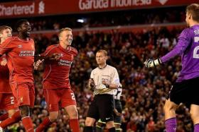 JUBILATION: Liverpool players rush towards their goalkeeper Simon Mignolet (above, right) after their epic penalty-shootout win over Middlesbrough.