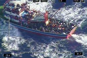 A handout image released by the Cyprus Defence Ministry on Sept 24 shows a large fishing trawler overloaded with people in the Mediterranean Sea.