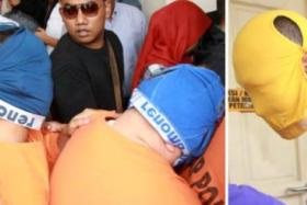 Some Malaysian customs officers trying to hide their faces with underwear.
