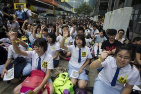 Secondary school students displaying yellow ribbons on their wrists  during a rally outside government headquarters in Hong Kong.