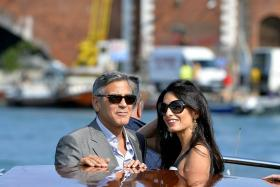 US actor George Clooney and his Lebanon-born British fiancee Amal Alamuddin taking a taxiboat upon arriving in Venice on Friday, the eve of their wedding.