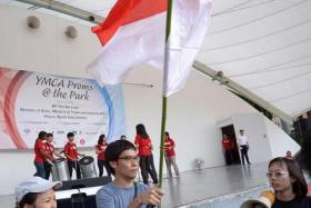 Bloggers Roy Ngerng (with flag) and Han Hui Hui (right) march to the stage area during a charity carnival for YMCA beneficiaries at Hong Lim Park on Sept 27, 2014.