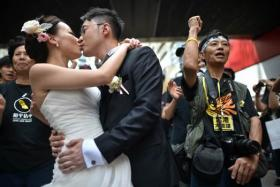 A couple take wedding photogtaphs in front of pro-democracy protesters in Hong Kong on October 1, 2014.