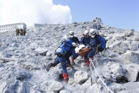 Firefighters carrying a hiker during rescue operations near the peak of Mount Ontake,