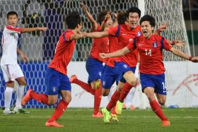 South Korea's midfielder Kim Young Uk (right) and South Korea's defender and captain Jang Hyun Soo (second from right) celebrate with team-mates after the winning goal.