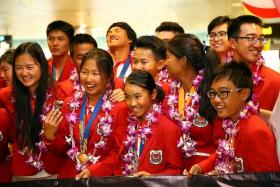 HOME SWEET HOME: The Singapore sailing contingent (above) receiving a warm welcome home at Changi Airport yesterday after their exploits at the Asian Games in Incheon, South Korea.