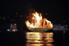 SMOKE ON THE WATER: Wishes of devotees are pasted on a boat made of paper, which is then set ablaze and sent to the sea.