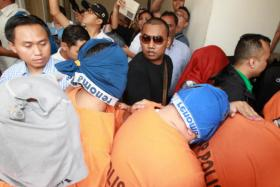 Fifteen customs officers being remanded at the Petaling Jaya Magistrate's Court created a scene when some of them donned underwear on their heads in an attempt to hide their identities.