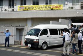A van carrying a 15-year-old high schoolgirl, who was arrested on suspicion of killing a school friend at her home, leaves a police station for the prosecutor's office in Sasebo in Nagasaki prefecture, on Japan's southern island of Kyushu on July 28, 2014.