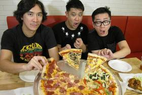 SLICED: (From left) Drummer William Lim, guitarist Dave Tan, and bassist Desmond Goh, tuck into a giant pizza.
