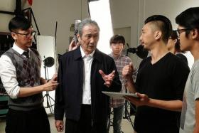 GETTING READY: Veteran actor Lim Kay Tong (middle, with director Randy Ang, in black) is in full make-up and costume during an imaging session to get into the role of Mr Lee Kuan Yew for the movie 1965.
