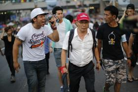 Pro-democracy protesters arguing with a  man (centre) as he walks away from an area blocked by protesters outside the government headquarters office in Hong Kong on Thursday.
