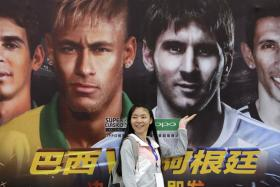 A Chinese fan stands in front of a poster promoting Brazil and Argentina's glamour friendly in Beijing.