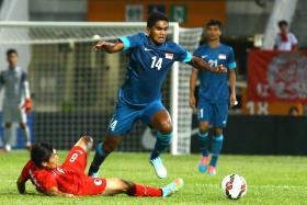 Singapore midfielder Hariss Harun tries to evade a tackle from Hong Kong's Huang Yang.