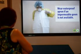 A health worker watching a video showing the safety instructions when treating an Ebola patient during the national Ebola virus disease summit in Manila on Friday.