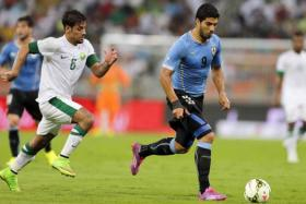 Luis Suarez (right) runs with the ball as Saudi Arabia's Mustafa Al Bassas chases during their friendly football match at King Abdullah stadium in Jeddah October 10, 2014.