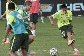 Brazil's forward Neymar (right) kicks the ball during a football training session at the National Stadium on October 13, 2014. Brazil will play Japan in a friendly match on October 14.