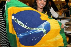 DIE-HARD FAN: Ms Mariana Melo showing her support for the Brazilian national team during their arrival at Changi Airport.
