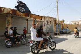 File photo of a supporter of the Islamic State of Iraq and Syria (ISIS) waving their flag.