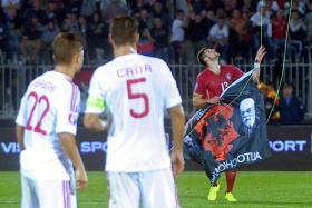 Albania's players look at Serbia's defender Stefan Mitrovic grabbing a flag with Albanian national symbols from remotely operated drone flown over the pitch during the EURO 2016 group I football match between Serbia and Albania.