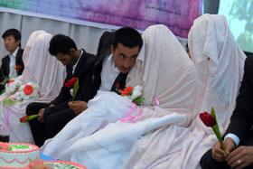 An Afghan groom (C) talks to his bride during a mass wedding ceremony in which one hundred couples were married on the outskirts of Kabul.