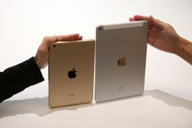 The new iPad Mini 3 (left and iPad Air 2 (right) on display during an Apple special event on Thursday in Cupertino, California.