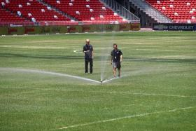 CRUCIAL: Workers tending to the pitch at the National Stadium. The condition of the grass has come under fire with the Suzuki Cup looming.