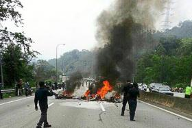 The burning wreckage of one of the motorcycles following the accident along the Karak Highway, which links Kuala Lumpur to the east coast of Malaysia.
