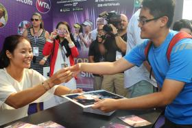 CENTRE OF ATTRACTION: Li Na obliging autograph hunters at the WTA Finals fan festival outside the Indoor Stadium yesterday.