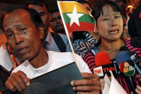 Mr Tun Tun Htike (left) and Madam May Thein, parents of Win Zaw Htun, one of two Myanmar workers accused of killing British tourists, crying while speaking to reporters after arriving in Bangkok on Wednesday.