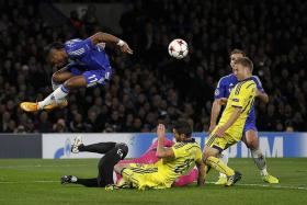 MAKING THE LEAP: Didier Drogba jumping to avoid clashing with Maribor's Slovenian goalkeeper Jasmin Handanovic (in pink).