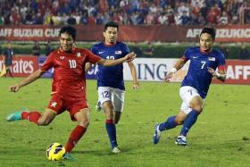 RIVALS: Thailand (in red) and Malaysia, who faced each other in the semi-finals of the Suzuki Cup two years ago (left), insist on playing on a grass surface at this year's tournament, scheduled to be held in Singapore.