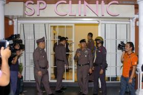 Thai police officers at the Bangkok beauty clinic where the 24-year-old British woman died after undergoing cosmetic surgery.