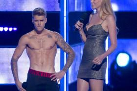 "Singer Bieber takes his shirt off as he and model Stone introduce an act during the ""Fashion Rocks 2014"" concert in the Brooklyn borough of New York."