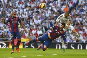 WEAKNESS: (From right) Karim Benzema getting the better of Barca defenders Gerard Pique and Dani Alves.
