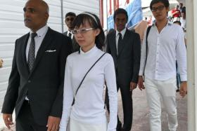 Roy Ngerng (rear, right) and Han Hui Hui (front right) with their lawyer M Ravi (front left) leave the State Court building in Singapore on October 27, 2014.