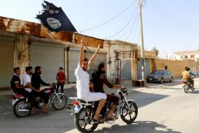 A man in north-east Syria waving a flag in support of militant group Islamic State of Iraq and Syria (ISIS) in August.