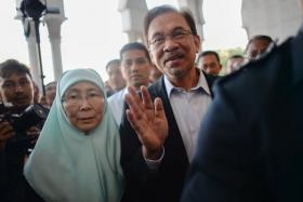 Malaysian Opposition leader Anwar Ibrahim (C) waves as his wife Wan Azizah (L) acompanied him before entering the court in Putrajaya on October 28.