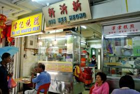 HORROR: Wong Keng Foong took the chopper from Madam Elita Sukirman's roast meat stall (above).