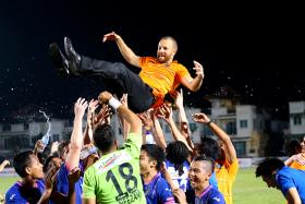 KEY MEN: Players and officials throwing Alex Weaver (in orange) in the air to celebrate their league triumph, which came after Hafiz Rahim's solitary goal sealed a 1-0 win over Albirex last night.