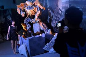 ROLL OUT: A visitor gets her picture taken with Bumblebee during the Transformers 30th Anniversary Exhibition at the Singapore Science Centre.