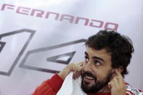 Ferrari Formula One driver Fernando Alonso of Spain smiles inside his garage before the start of the second free practice session of the Brazilian F1 Grand Prix at Interlagos circuit.