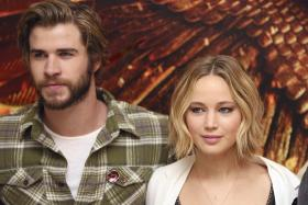 Jennifer Lawrence with 'The Hunger Games: Mockingjay Part 1' cast member Liam Hemsworth at the London photo call in her stylish hairdo.