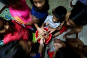 SEPARATE LIVES: Madam Rafeah Abdul Kadir's children share whatever they get, like this bowl of fish crackers.
