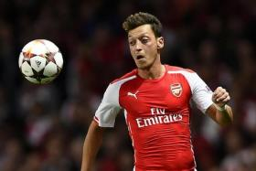 Arsenal's Ozil runs for the ball during their Champions League playoff match against Besiktas at the Emirates stadium.