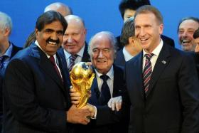 The Emir of the State of Qatar Sheikh Hamad bin Khalifa Al-Thani (left), Fifa president Joseph Blatter (centre) and Russia's Deputy Prime Minister Igor Shuvalov pose with the World Cup after winning  their bids to host the tournament.