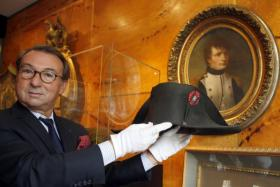 Auctioneer Jean-Pierre Osenat displays a black felt two-cornered hat belonging to French Emperor Napoleon Bonaparte at their auction house in Paris.